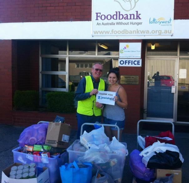 Foodbank WA receiving thousands of items of food from Carmel School. Rachel Barrett from JAA hands over the food at the Foodbank head office.